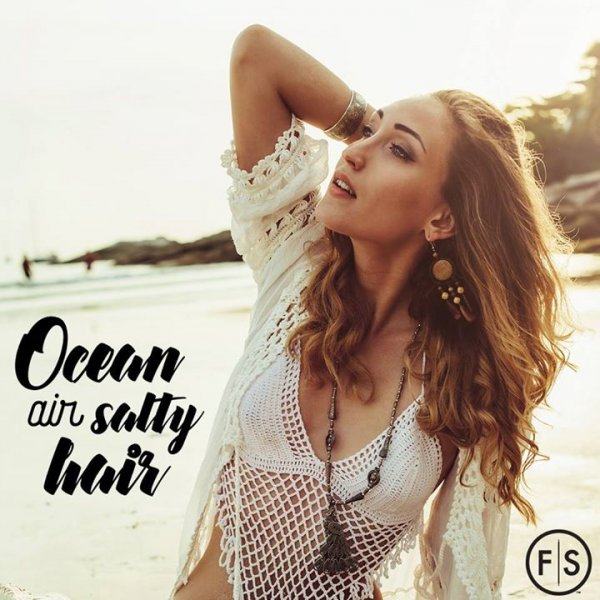 "Girl on a beach posing with wavy hair with the text ""ocean air salty hair"" in the bottom left hand corner"