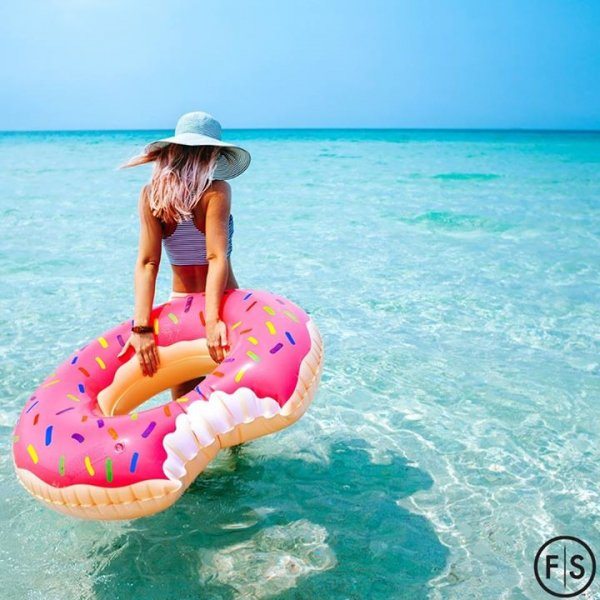 Girl wearing a sunhat knee-deep in ocean water holding a donut float