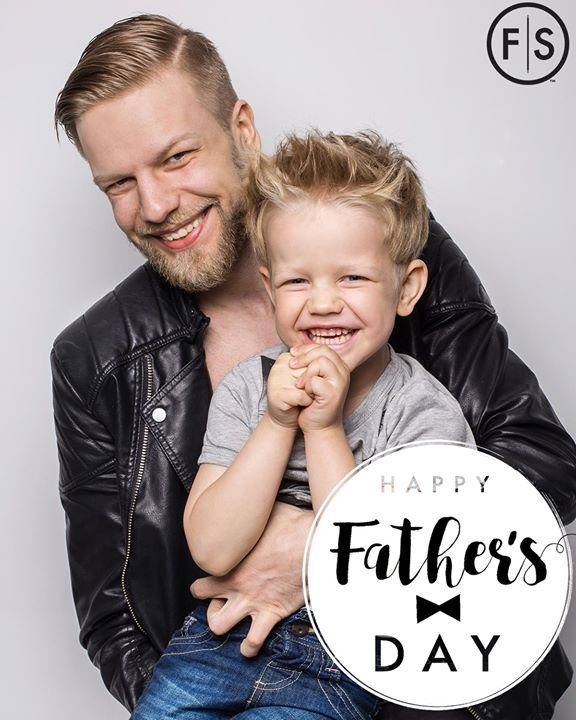 "Picture of a father with his son on his lap with the text ""Happy Fathers Day"" in the bottom right corner"
