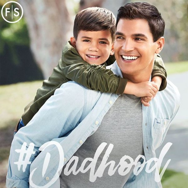 Dad holding young son on his back with the hashtag #Dadhood in white lettering on the bottom