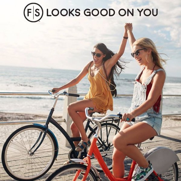 "Two girls riding bikes on beach and holding hands with ""FS Looks Good On You"" at top of image in black"