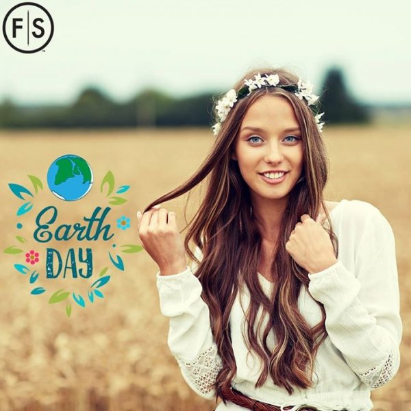 "Woman with long brown hair standing in field with flower crown on and ""Earth Day"" written to her left"