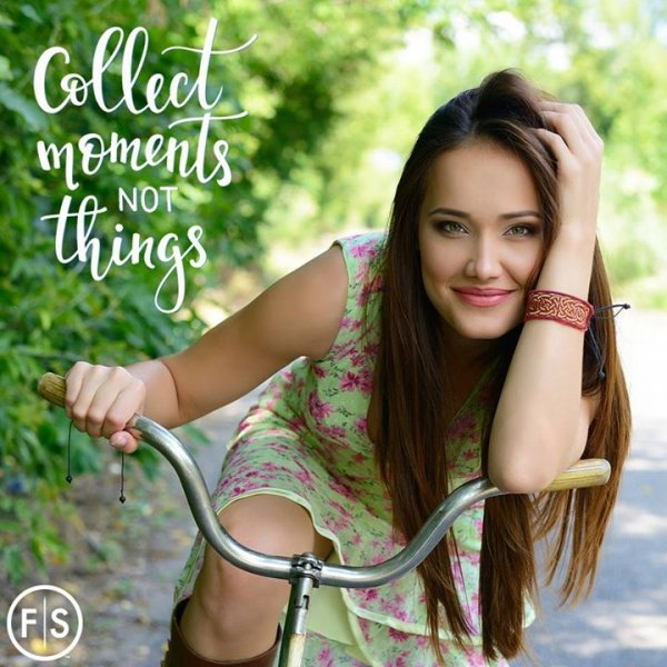 "Woman with long brown hair sitting on bike with ""Collect Moments Not Things"" written in white to left of woman"