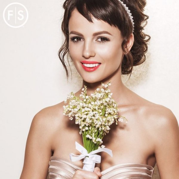 Brunette girl in pink dress holding flower bouquet