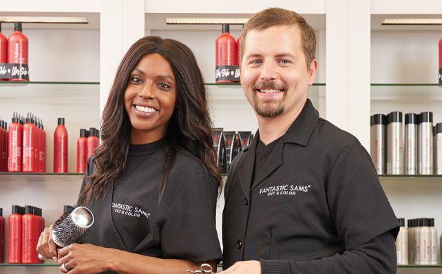 ethnic female stylist and caucasian male stylist in salon