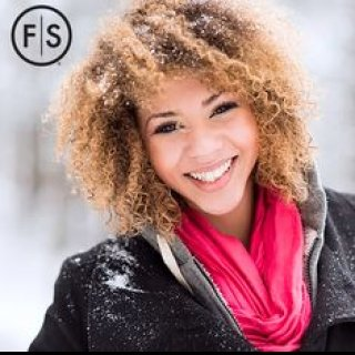 Woman with curly hazelnut colored hair standing outside smiling in the snow