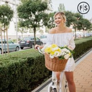 Young blonde woman riding a bike with a basket of flowers