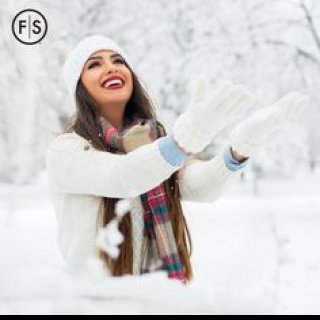 Long haired brunette wearing a white sweater, hat and gloves throwing snow in the air