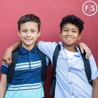 Two young boys on the first day of school, smiling with their arms on each others shoulders