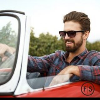 Brunette man wearing sunglasses driving a convertible with the top
