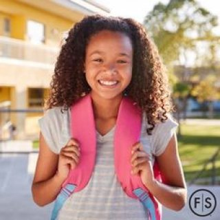 Little girl with curly brown hair wearing a pink backpack smiling