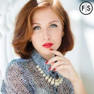 Woman with red hair wearing gray sweater looking at camera