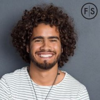 Young man with curly hair smiling