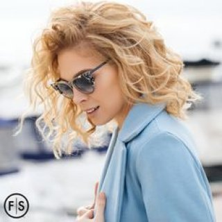 Blonde woman with curly hair wearing sunglasses and blue jacket looking down