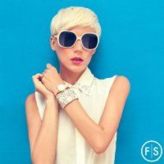 Blonde girl with a short pixi hair cut posing with sunglasses on