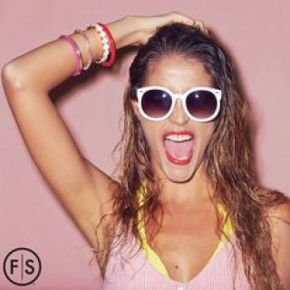 Girl wearing sunglasses sporting beachy waves with the Fantastic Sams logo on the bottom left corner
