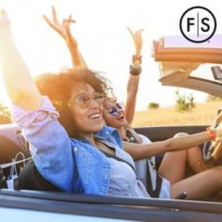 Two young girls smiling with their hands up in a convertible car