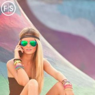 Blonde girl wearing sunglasses dressed in a boho style