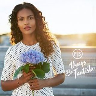"Woman in white and black polka dot top holding blue flowers in her hand with ""Always Be Fantastic"" written in white to the right of the woman"