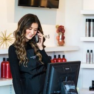 FS Blog - Women standing at front desk answering phone in salon