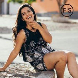 Brunette girl sitting on ground smiling